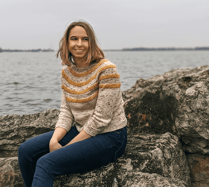 Rachel sitting on a boulder in front of Lake Erie, wearing a sweater and jeans.